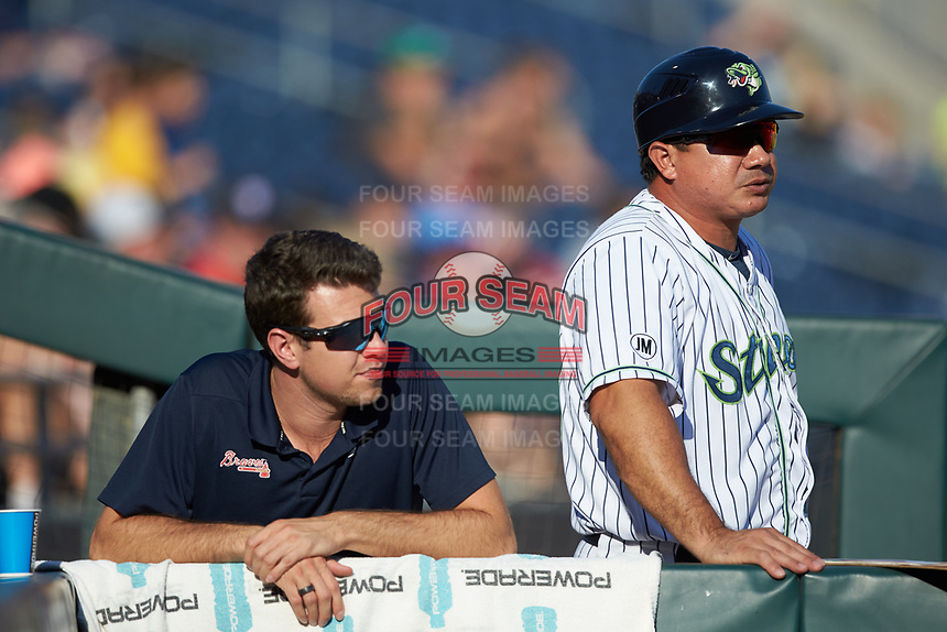 (L-R) Gwinnett Braves athletic trainer Nick Jensen and coach Einar Diaz (28) watch from the dugout during the game against that Scranton/Wilkes-Barre RailRiders at BB&T BallPark on August 17, 2019 in Lawrenceville, Georgia. The Stripers defeated the RailRiders 8-7 in eleven innings. (Brian Westerholt/Four Seam Images)