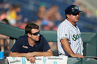 (L-R) Gwinnett Stripers athletic trainer Nick Jensen and coach Einar Diaz (28) watch from the dugout during the game against that Scranton/Wilkes-Barre RailRiders at Coolray Field on August 17, 2019 in Lawrenceville, Georgia. The Stripers defeated the RailRiders 8-7 in eleven innings. (Brian Westerholt/Four Seam Images)