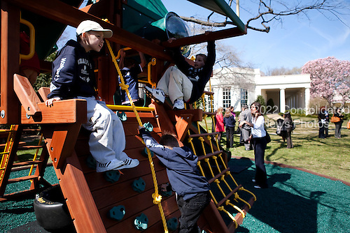 Washington, DC - March 24, 2009 -- After greeting children and officials of the Children's Miracle Network at the White House, March 24, 2009, the President invited the children to try out his daughters' new swing set on the edge of the Rose Garden. The Oval Office can be seen in the background..Mandatory Credit: Lawrence Jackson - White House via CNP