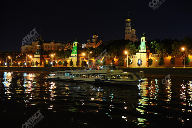 The Kremlin stood behind a pleasure boat that cruised the Moscow river. Moscow, Russia, July 11, 2009
