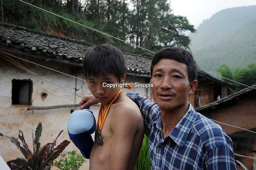 Pan Guang Wei, 15 with his father, in their farmhouse in Honggi Village in the mountains of Sichuan Province, China. The young boxer are hoping to make it to become some of China's first professional boxers...PHOTO BY SINOPIX