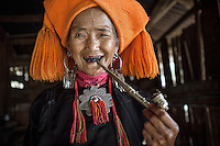 "Portrait of an old Wa women smokes pipe in her house. The Wa, which literally means ""mountain dwellers"", is the hilltribe that inhabit the Sino-Burmese. Known as one of the last headhunting tribe until mid-twentieth century, their population in both countries now approximately no more than one million. In the homogenous society of modern China, Wa is one of more than 50 officially state-recognized ethnic minorities. They can be found around the southwestern corners of Yunnan province."