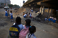 Students of the Kartini Emergency School wait for the 'Twin Teachers' beside the elevated highway where classes are held. Since the early 1990s, twin sisters Sri Rosyati (known as Rossy) and Sri Irianingsih (known as Rian) have used their family inheritance to set up and run 64 schools in different parts of Indonesia, providing primary education combined with practical skills to some of the country's most deprived children.   .