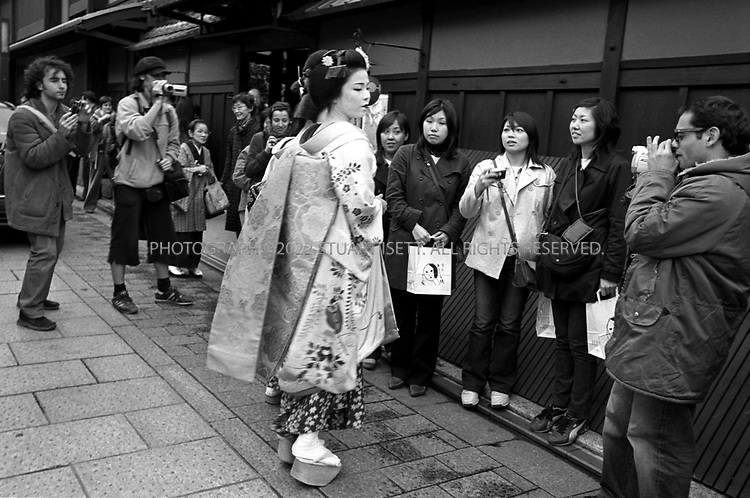 November, 2003--Kyoto, Japan..Japanese and foreign tourists crowd around a geisha arriving in the Gion to visit tea houses...All photographs ©2003 Stuart Isett.All rights reserved.This image may not be reproduced without expressed written permission from Stuart Isett.