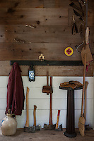 The rough wood cladding in the hallway is lined with an assortment of essential hatchets and axes of varying sizes
