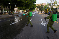 HAVANA, CUBA - April 15: Cuban soldiers wearing face masks walk to disinfect sidewalks and streets in downtown in Havana, Cuba, on April 15, 2020. The military soldiers carry out a disinfection process in the city, applicable in parks, commercial areas, atriums, transportation stations and general public meeting places  decreed by the Government to contain the expansion of COVID. 19. (Photo by Eliana Aponte/VIEWpress)