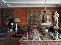 The open plan living area is an exotic array of decorative arts, with 19th century paintings and sculptures jostling for space with Ottoman bowls and Chinese vases
