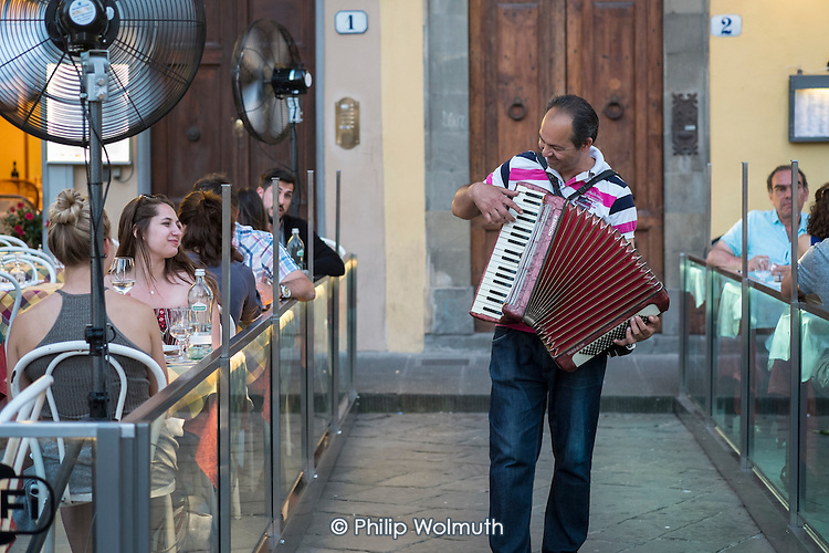 Street musician plays to tourists in a restaurant, Florence, Italy