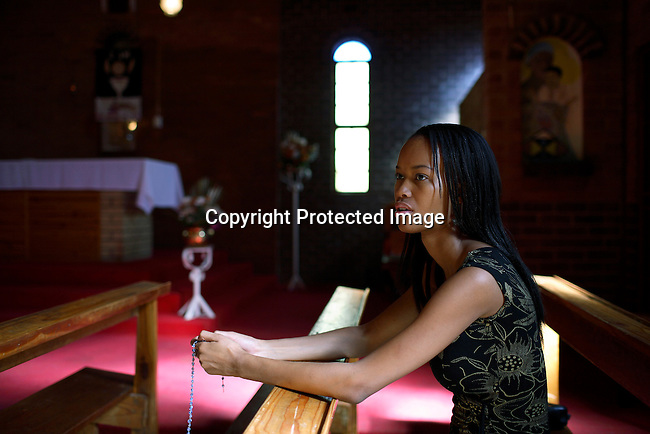 Dorah Mtetwa, age 22, an university student prays in the Catholic church.