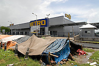 INDIA Westbengal Calcutta Kolkatta, new Metro whole sale market and huts of squatter  / INDIEN Westbengalen, Megacity Kolkata Kalkutta, Neubau Metro Grosshandelsmarkt an einer bypass Road am Stadtrand von Calcutta , davor Huetten von Obdachlosen