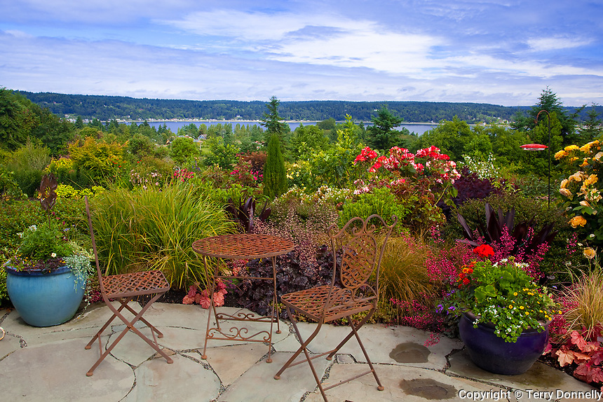 Vashon-Maury Island, WA<br /> Driscoll garden, iron table and chairs on flagstone patio with a view of Quartermaster Harbor