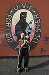 A child stands in front of murals painted by the Protestant community in Belfast, Northern Ireland.