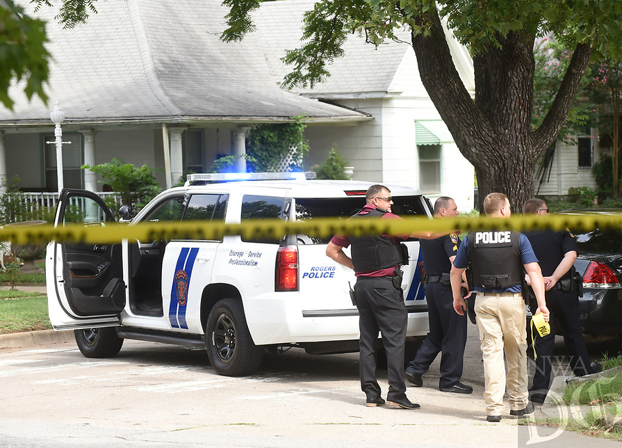 NWA Democrat-Gazette/FLIP PUTTHOFF <br />Rogers police gather Wednesday Aug. 8 2018 in front of a home near Third and Persimmon streets in Rogers where people barricated themselves in the home as police tried to serve a warrant on man. A standoff lasted approximately three hours. All occupants eventually surrended peacefully.