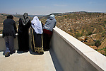 Palestinian women watch from a rooftop as an Israeli bulldozer uproots Palestinian olive trees during the construction of Israel's controversial West Bank barrier in the village of Al Walaja near Bethlehem on 08-06-2010.