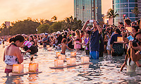 On Memorial Day, spectators photograph lanterns floating in the ocean during the 15th Annual Lantern Floating Ceremony at Ala Moana Beach Park, Honolulu, O'ahu.