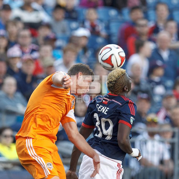 Houston Dynamo defender A.J. Cochran (16) and New England Revolution midfielder Saer Sene (39) battle for the ball. In a Major League Soccer (MLS) match, the New England Revolution (blue/white) defeated Houston Dynamo (orange), 2-0, at Gillette Stadium on April 12, 2014.