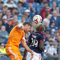 Houston Dynamo defender A.J. Cochran (16) and New England Revolution midfielder Saer Sene (39) battle for the ball. In a Major League Soccer (MLS) match, the New England Revolution (blue/white) defeated Houston Dynamo (orange), 2-0, at Gillette Stadium on April 12, 2014.