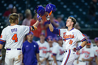 Logan Davidson (8) of the Clemson Tigers knocks helmets with teammate Grayson Byrd (4) as he crosses home plate after hitting a solo home run in the bottom of the fourth inning against the Duke Blue Devils in Game Three of the 2017 ACC Baseball Championship at Louisville Slugger Field on May 23, 2017 in Louisville, Kentucky.  The Blue Devils defeated the Tigers 6-3.. (Brian Westerholt/Four Seam Images)