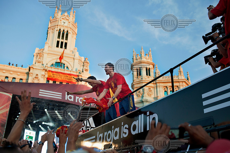A crowd cheers as players celebrate during the victory parade of the Spanish national football team who won the UEFA EURO 2012 competition.