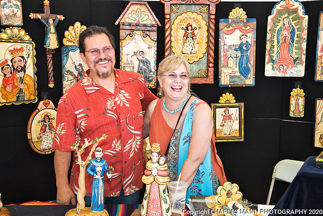 Artist Carlos J. Otero and his wife at their booth at the 2009 Spanish Market, and event held each July on the plaza in Santa Fe, New Mexico