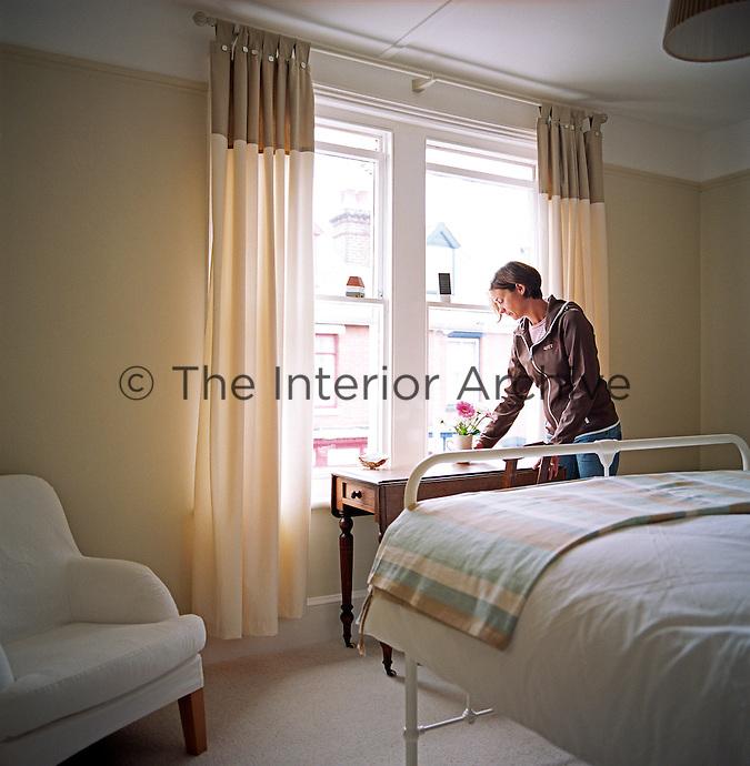 Interior designer Amanda Lambert arranging flowers in her bedroom
