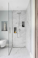 The marble clad shower unit with practical niches left for storing cleaning products