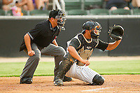 Kannapolis Intimidators catcher Miguel Gonzalez #32 sets a target as home plate umpire Roberto Ortiz looks on during the South Atlantic League game against the Delmarva Shorebirds at Fieldcrest Cannon Stadium on August 6, 2011 in Kannapolis, North Carolina.  The Intimidators defeated the Shorebirds 14-6.   (Brian Westerholt / Four Seam Images)