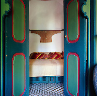 A view past a pair of blue and green painted doors give a view to the bed, which is from a 'house of pleasure' in Canton. On the walls are the robes of Mandarins. The ancient floor mosaics are in black and white.