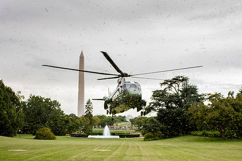 Fresh cut grass clippings fly up from the South Lawn of the White House as President Barack Obama arrives aboard Marine One on August 26, 2012 in Washington, DC. Obama was returning from a weekend stay at Camp David. .Credit: Pete Marovich / Pool via CNP