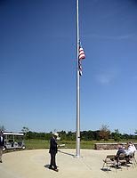 With the american flag at half mast, Gregory J. Whitney, Director of Washington Crossing National Cemetery speaks during a ceremony to commemorate the end of World War II or VJ Day Friday August 14, 2015 in Newtown, Pennsylvania. (Photo by William Thomas Cain)
