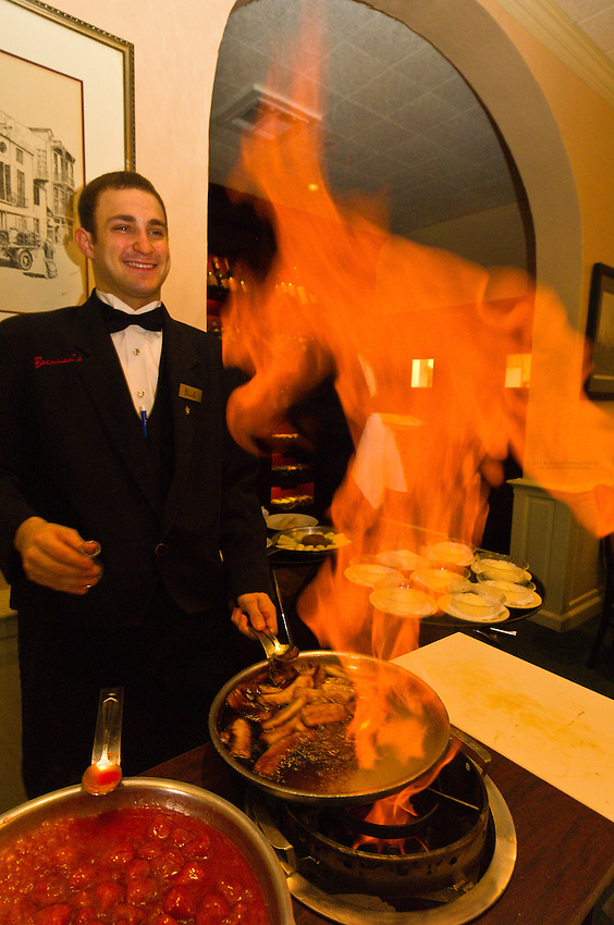 A waiter (Billie Hartline) flambeing desserts (Crepes Fitzgerald on left and Bananas Foster on right), Brennan's Restaurant in the French Quarter, New Orleans, Louisiana, USA