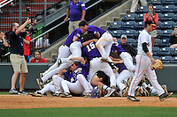 Members of the Western Carolina Catamounts jump on the victory dog pile following walk-off 3-2 win against Mercer in the SoCon Tournament championship final on Sunday, May 29, 2016, at Fluor Field at the West End in Greenville, South Carolina. Mercer first baseman Hunter Bening (44) walks past. (Tom Priddy/Four Seam Images)