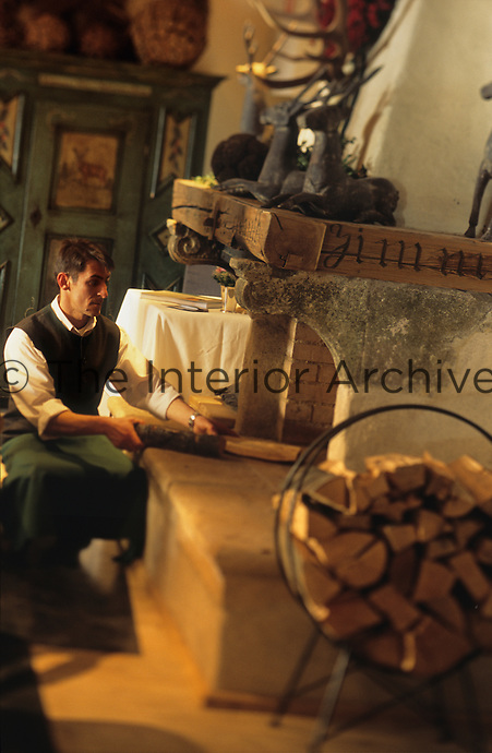 A member of staff at the Hotel & Spa Rosa Alpina preparing logs for the fire in the dining room