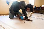 Transfert de technologie. Badou, artiste peintre qui a d&eacute;j&agrave; expos&eacute; en France, se reconvertit partiellement en d&eacute;coupeur de toile de spi sous le regard de St&eacute;phane.<br /> <br /> a kite for rescue the artisans fishermen of Senegal this is the dream of Stephane Blanco.<br /> St&eacute;phane Blanco shows at Badou  how to cut the differents pieces of the kite