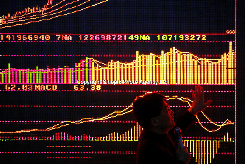 A portfolio manager speaks to investors to explain the recent slide and rebound in the Shanghai Index while standing in front of a trading board at a local securities exchange house in Shanghai, China. Chinese Exchange lost 3,000 points, almost nine percent of its value yesterday. China has a wild roller-coaster stock market but this is one of the largest single day drops..28 Feb 2007