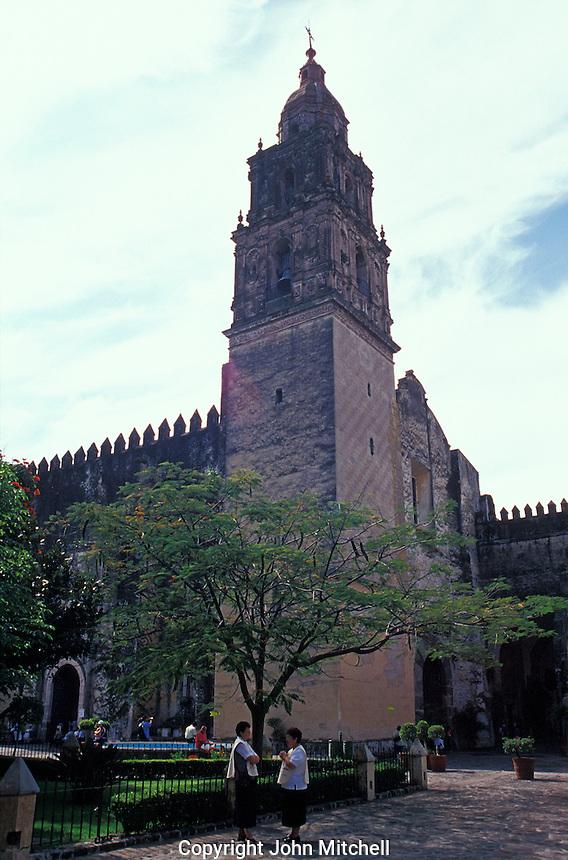 Two women chatting beside the 16th-century cathedral or Templo de la Asuncion de Maria in Cuernavaca, Morelos, Mexico.