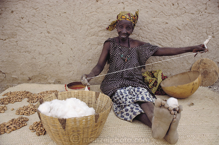 Most women in Africa are excellent multi-taskers. Here a woman offers peanuts for sale to passersby on a dirt path in the village of Kouakourou, Mali, and uses the time between customers to spin cotton thread. Material World Project.