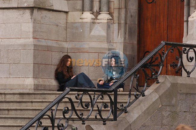 Two young girls sit at the side door having a cigarette at St Peters Church in Drogheda .Photo Fran Caffrey Newsfile.ie..This Picture has been sent to you by Newsfile Ltd..The Studio,.Millmount Abbey,.Drogheda,.Co. Meath,.Ireland..Tel: +353(0)41-9871240.Fax: +353(0)41-9871260.ISDN: +353(0)41-9871010.www.newsfile.ie..general email: pictures@newsfile.ie