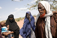 Kenya - Dadaab – 21st July 2011. Abdi Omar (right), 80 years old, comes from the Somali village of Afmathow, in Lower Juba region. He arrived five days ago after a 15 day trip, partly on foot and part on a vehicle, with his wife and eight children and grandchildren. In Somalia he used to have more than one hundred goats and than ten cows. Most of them died, he sold the remaining ones to raise money for the trip.