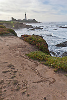 "Discovered in the sand one Sunday morning, a drawing of a person saying, ""Aah"" and below it, this message, ""I watched the sun set.""   In the background is Pigeon Point Lighthouse."