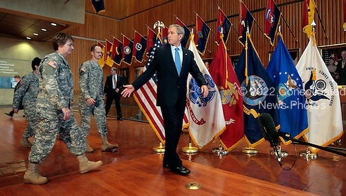 WASHINGTON - DECEMBER 20:  (AFP OUT) U.S. President George W. Bush (R) leads a group of U.S. Army nurses, doctors and administrators before making a statement after visiting injured troops at Walter Reed Army Medical Center December 20, 2007 in Washington, DC. The visit was closed to the press and follows a visit to The National Naval Medical Center in Bethesda, Maryland, the previous day.  (Photo by Chip Somodevilla/Getty Images)