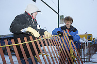 Saturday March 6 , 2010    Volunteers put up snow-fencing along 4th avenue in the early hours just prior to the ceremonial start of the 2010 Iditarod in Anchorage , Alaska