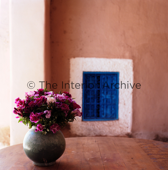 A ceramic vase filled with fresh flowers on a wooden table against a blue shuttered window with a whitewashed frame