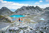 Two trail runners looking at the turquoise water of the Wildsee, below the Pizol, Switzerland