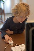 Little girl using a desktop computer at home.