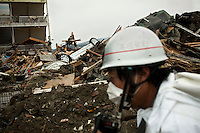 A rescue worker walks in front of upturned cars and damaged buildings. Thousands of people died in this small town which ran out of body bags. On 11 March 2011 a magnitude 9 earthquake struck 130 km off the coast of Northern Japan causing a massive Tsunami that swept across the coast of Northern Honshu. The earthquake and tsunami caused extensive damage and loss of life.