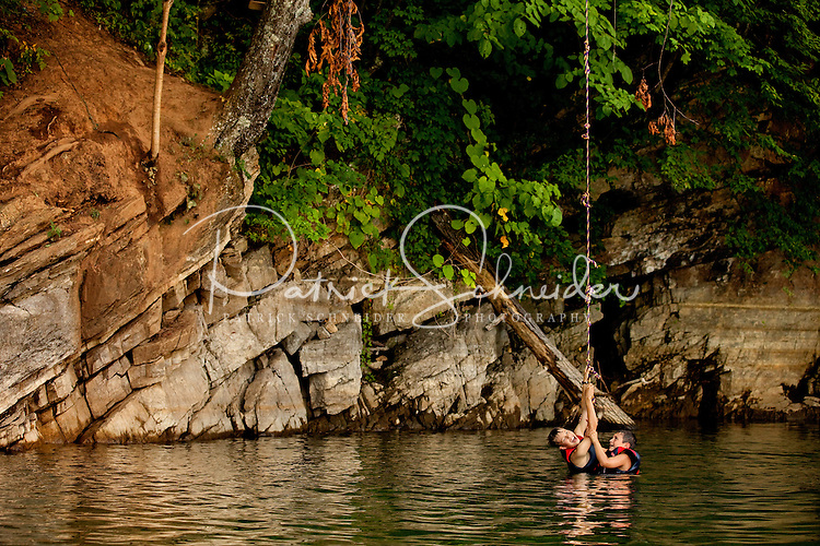 Two boys, both wearing personal floatation devices, try to climb up a rope that is hanging down from a tree. The rope is used by many to swing into the lake. Photo taken at Watauga Lake in Tennessee.
