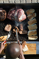 "MABONENG, SOUTH AFRICA - MARCH 20: A man grills meat at a traditional ""braai"" in Maboneng district on March 20, 2016 in downtown Johannesburg, South Africa.  A former derelict industrial area, and a no-go area after dark, it is now a vibrant area with artists, businesses, galleries and tourists. A racially mixed cultural hub with markets on the weekend. Maboneng is the idea of young entrepreneur Jonathan Liebmann, and he owns and controls most of the buildings in the area. (Photo by Per-Anders Pettersson/Getty Images)"