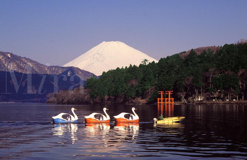 Honshu. Hakone.   Mount Fuji over Lake Ashi.  Torii arch or gate (shrine)  and string of swan shaped pleasure boats..