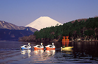 Honshu. Hakone.   Mount Fuji over Lake Ashi.  Torii arch or gate (shrine)  and string of swan shaped pleasure boats..
